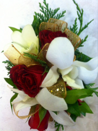 Christmas wrist corsage with red roses, orchids and wintergreens